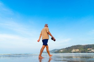 a pensioner walking on a sunny beach